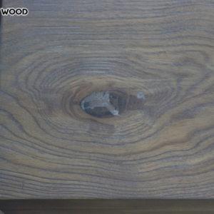 La photo d'une partie d'une table en bois avec une huile grise couvrante